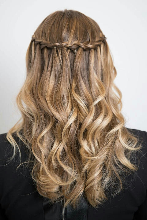 Create a center part (since this hairstyle looks more even that way) and French braid from the right side of the part to your temple. Then, holding the three strands, continue French braiding but drop the outermost section of the braid