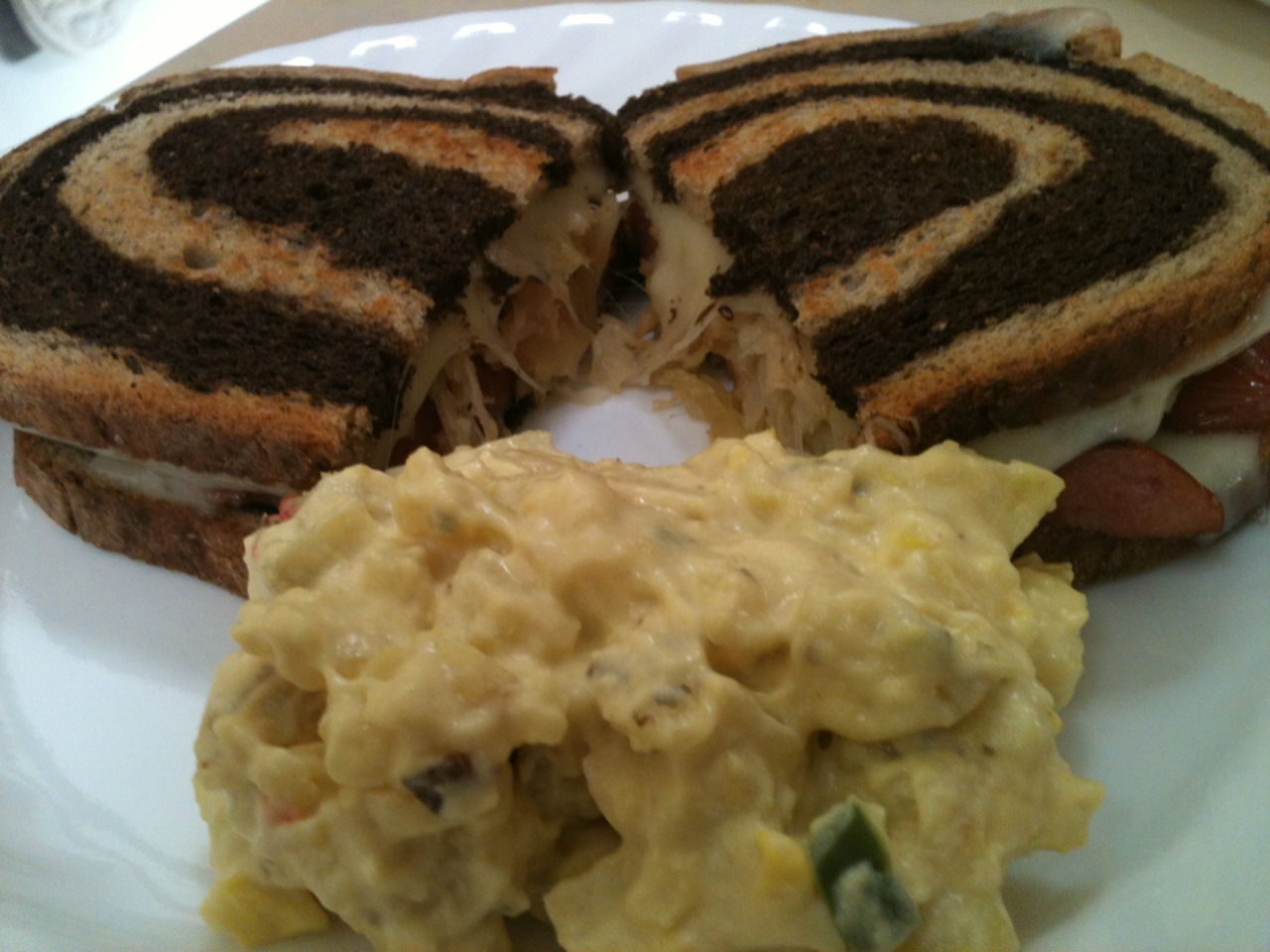 Grilled polish sausage with sour kraut  Swiss cheese with pumper nickel swirl bread.and a side of mustard potato salad