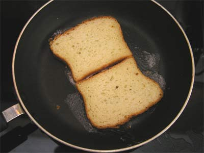 When scrambledeggs are done cooking, start frying the bread. Fry bread on both sides.
