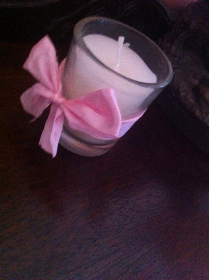 Wrap the ribbion around the candle and make it into a bow... There you go a beautiful candle with nearly no cost atall!!