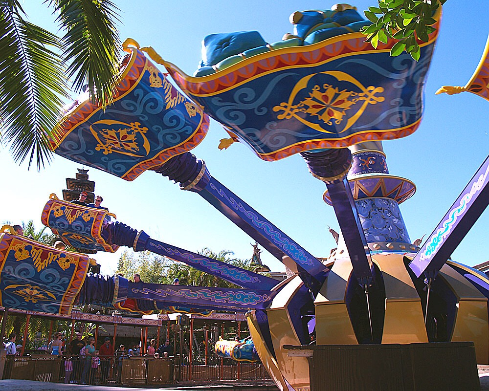 The Magic Carpets of Aladdin Fly high over Agrabah on a magic carpet around a giant genie lamp.  Height: Any FP+: Yes