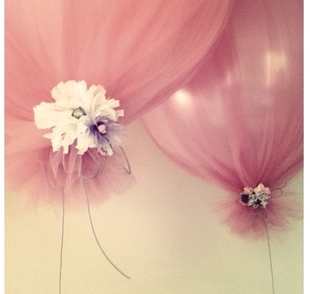 --> Balloons covered in tulle tied with ribbon and flowers.