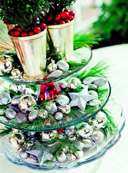 Three tiers!  Fill the hollow stems of stacked clear-glass cake plates with cranberries. Silver ornaments, spray-painted silver nuts and evergreen sprigs line the plates; a trio of tiny trees garnished with cranberries rests on the top layer.