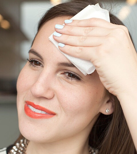 Blot your face in a pinch with a clean toilet seat cover.  Initially, yes, this sounds gross, but both blotting papers and toilet seat covers are made out of similar fabrics and will help sop up excess oil on your skin.