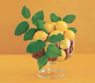 Sunlit The elements: One dozen lemons (about $7), one pound hazelnuts (about $5), and three small branches of lemon leaves.  The container: Any glass bowl―preferably with a pedestal, for added drama―such as this clear glass compote.  The tip: Juxtaposing large, smooth, shiny objects (lemons) with