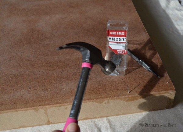 Lay the tempered hardboard on top and nail it down with 5/8″ brad nails. Nail the corners with 1″ brad nails. Countersink the nails and fill the holes with wood filler. After the wood filler is dry, give the frame a light sanding. Prime the frame if you are using a light-colored fabric.