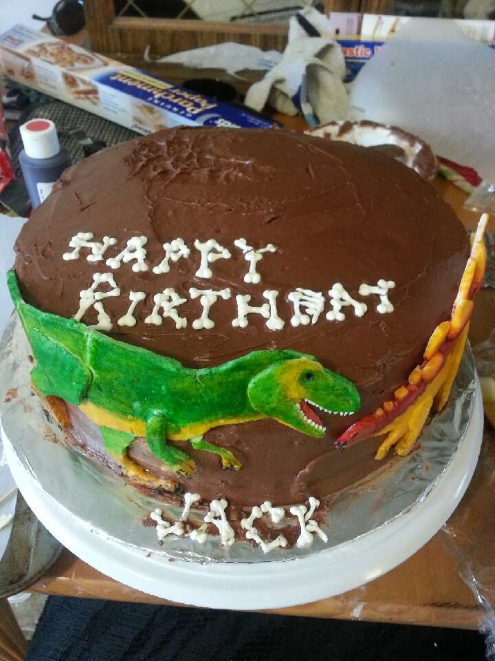 Iced the cake with chocolate frosting then stuck the dinosaurs to it. I used a couple toothpicks to keep them from sliding (make sure to remove the tooth picks before serving! ) layed the bones I made on the cake to read happy birthday jack. Put my columns in the bottom cake.