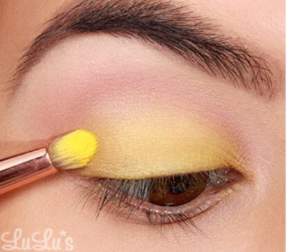 3. Next, apply a bright yellow eyeshadow to the upper lid just below the crease using an eyeshadow brush.