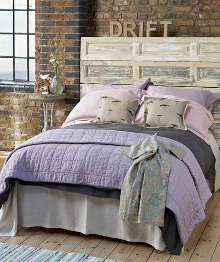 Organic Oasis An exposed brick wall in a bedroom can feel cool, yet a little cold. Pull it together with a few charming decorative choices like a reclaimed door headboard and lavender quilted comforter.