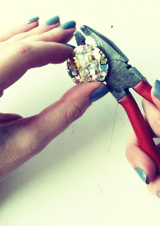 Cut or bend the back of the earring off with wire cutters, tweezers or really strong scissors.