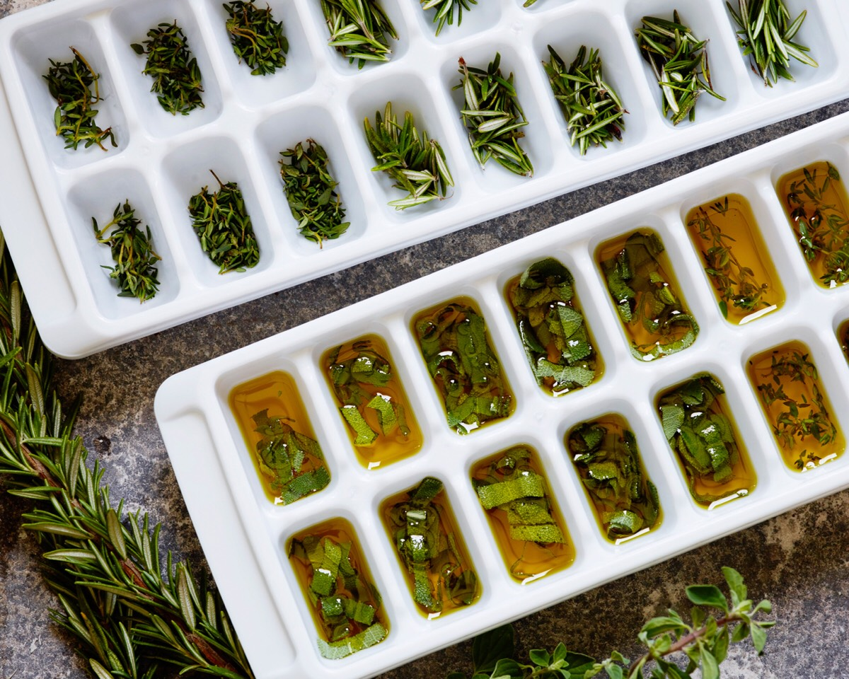 Carefully remove the herbs from any stalks, roughly chop larger pieces, and place them in an ice cube tray. Fill each little section up halfway with herbs and then top with extra virgin olive oil.  Cover the tray with plastic wrap and freeze.