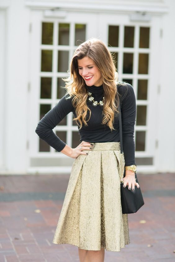 Items: 1.) Black Long Sleeved Turtle Neck  2.) Knee Length Flowy Gold Skirt 3.) Black Cross Body Purse 4.) Gold Watch 5.) Necklace