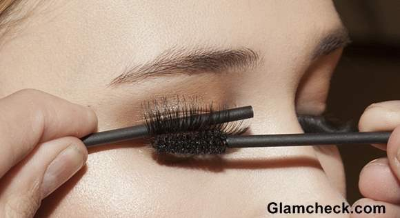 Use the back of a eyeshadow brush to gently hold the eyelashes in place as you use your mascara to blend your natural lashes into them.  Try wait 3-5 minutes before applying the mascara to your false eyelashes to allow the glue to dry as much as possible.