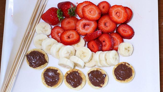 It doesn't get any easier than this. Slice the fruits, smear some Nutella on each of the pancake bites, and layer the ingredients onto the kabob sticks.