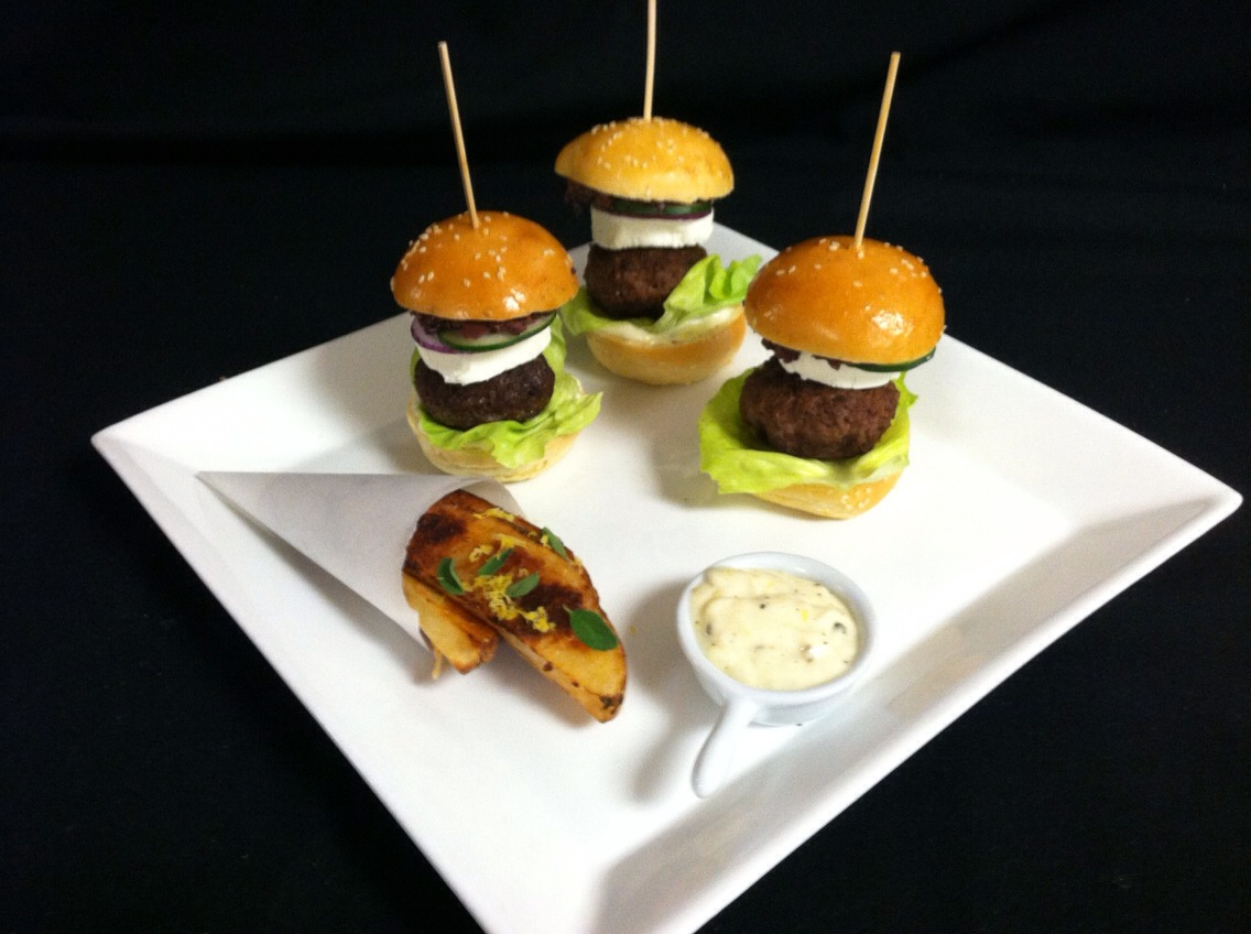 Greek sliders with ground lamb seasoned with minced fresh oregano on brioche bun with pickled red onion and cucumber, goat cheese, Kalamata olive tapenade, lemon oregano fries, and a black pepper and lemon aioli