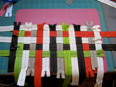 The project uses All Purpose Zippers and 8 steps in making a colorful purse from a bunch of individual zippers. First, you will need to lay out your pattern of creatively weaved zippers on the table, and pin in place, as you see in the image provided. Then, take each side and pin them (temporary)