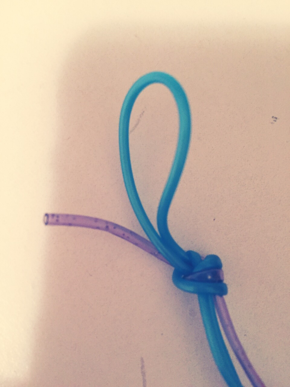 Make a simple knot with the long string doubled and the single string single like shown in the photo