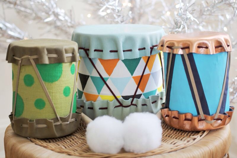 Supplies: tin cans, leather, decorative fabric, leather laces, Crop-a-dile, wooden dowel and ball, hot glue gun, and cotton. 1. Cut your fabric to fit around your tin can. Use Elmer's Glue to glue it in place.