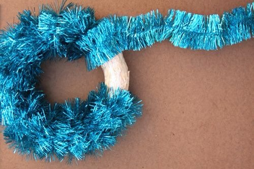 Purchase the tinsel and wreath form at your local craft store.   Wrap tinsel and secure with glue.   Add colorful ornaments and flowers to your taste.