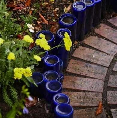 Bottle Garden Edging  For some decorative recycling, consider burying old bottles upside down to create edging for your garden beds and walkways. This example uses only cobalt blue glass, but bottles of any color would look just as striking.