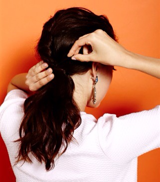 Once the twist is pinned, pull more hair back, twist to the right, and pin, so that they appear to be one big twist continuing down the back of your head. Once you reach the nape of your neck, tie the hair off onto a low ponytail with an elastic.
