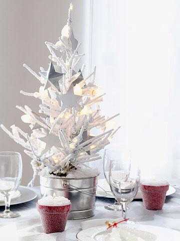 White Christmas  Make a mini tree the focal point of the dinner table. For a simple, dreamy look, use a white artificial tree. Anchor it in a tin pail and adorn with white lights and paper stars or other all-white ornaments.