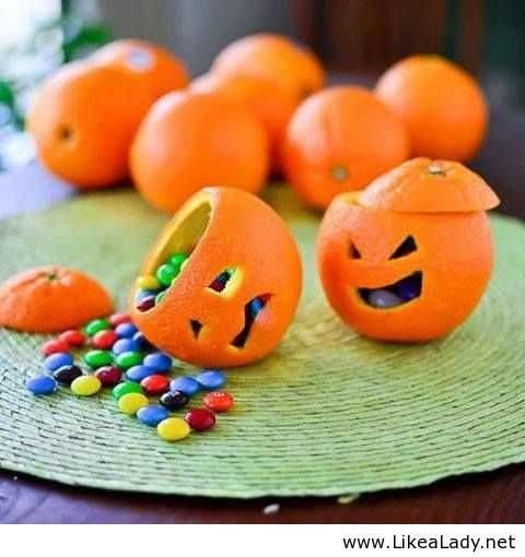 Open an orange by cutting off the to. Gut it with a spoon, use a small pumpkin saw or a small knife to decorate the face. Sketch it out first. Fill with m&ms and stage them. I've done this personally. It's a hit at parties.