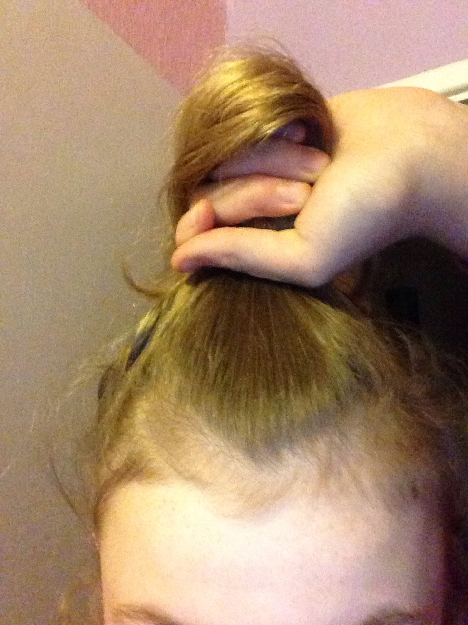 Put to the top of your head as if you are putting in a really high pony tail in your hair
