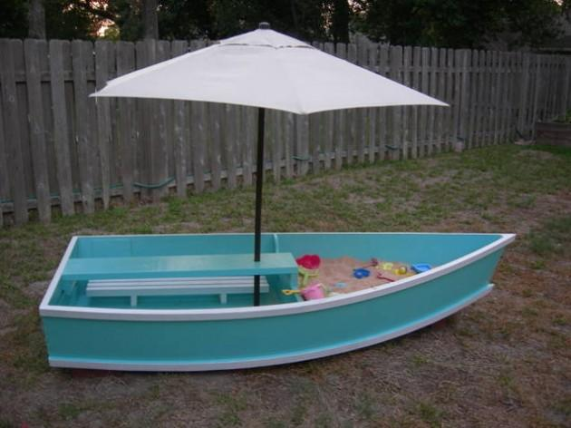 Kids' Playground  Create a new play place with an old boat, some sad and a patio umbrella! You could even fill it up with water in the summer time for them to cool down and have a splash pad!