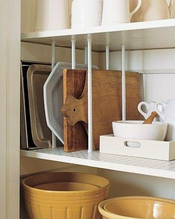 Instead of stacking your cutting boards, oven trays, and platters, use those short tension curtain rods to create dividers. Now you can place them upright for easy access and visibility.