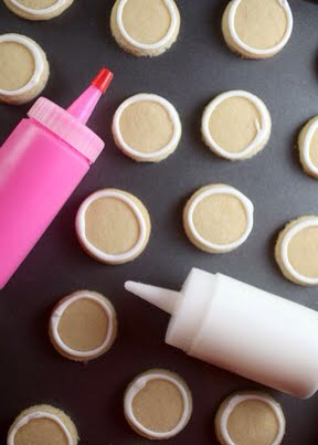 With a squeeze bottle, pipe and outline the cookies in white. Then thin the icing to create a flood consistency. Add a few drops of water at a time to the white icing until it is the consistency of thick syrup. Repeat with the pink icing.