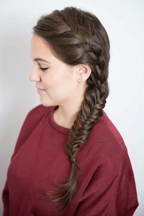 Curl your hair first for added texture, so the braid has more grip — you can even coat it with some hairspray. Next, create a deep part on the right (this will allow more braid to show straight on), and then pull your hair over your left shoulder.