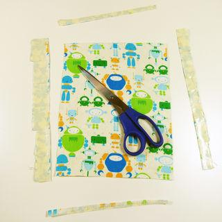 Begin by placing strips of duct tape along the back side of the fabric.  Slightly overlap the strips of tape.   Peel the fabric off the table and trim off the excess tape around the edges.