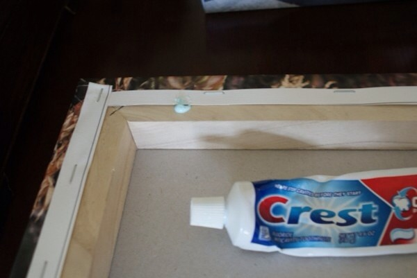 Add a dab of toothpaste to the back of the picture where the nail will go.