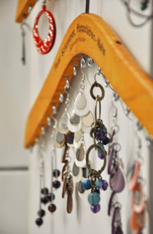 Clothes Jewelry Hanger Add a few eyelet screws to a wooden coat hanger and instant jewelry organization.
