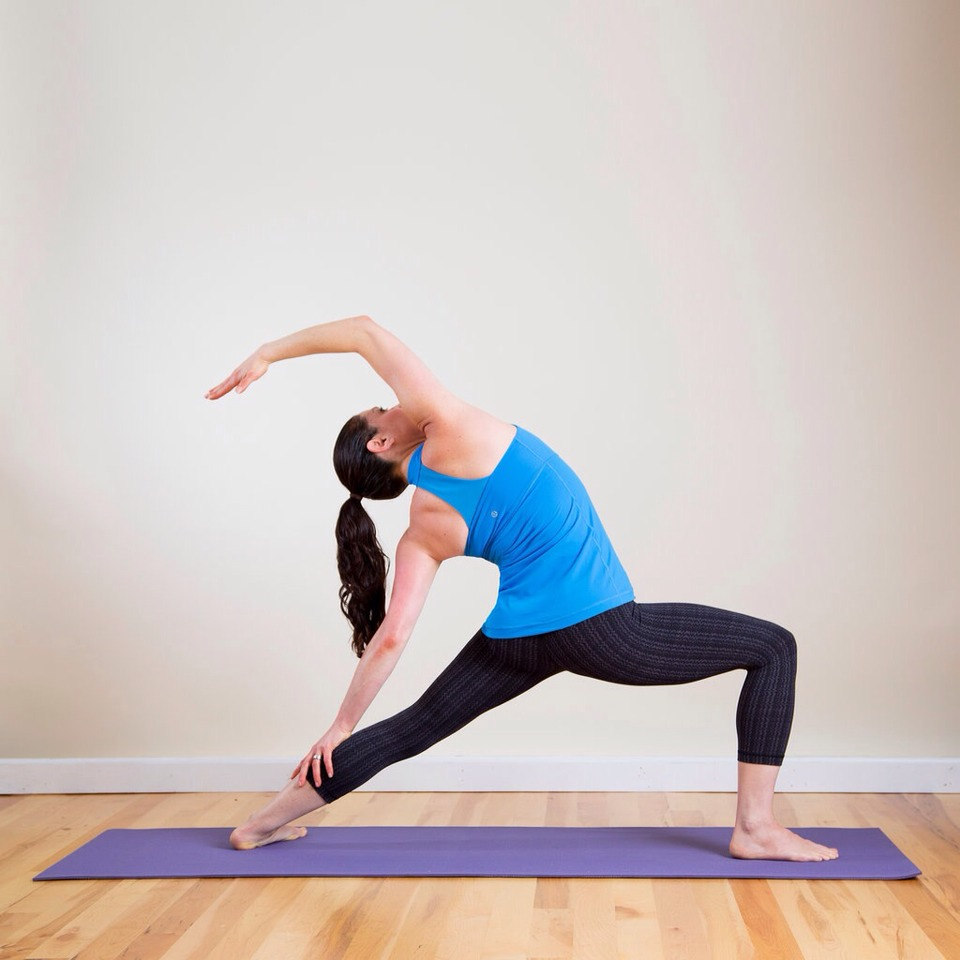 Reverse Warrior From Rotated Side Angle, inhale to lift the torso up. With an exhale, gently arch back and lower your left hand down, resting it on the back of your left leg. Raise your right arm overhead, feeling the stretch through the right side of your body. Continue to lower your hips.