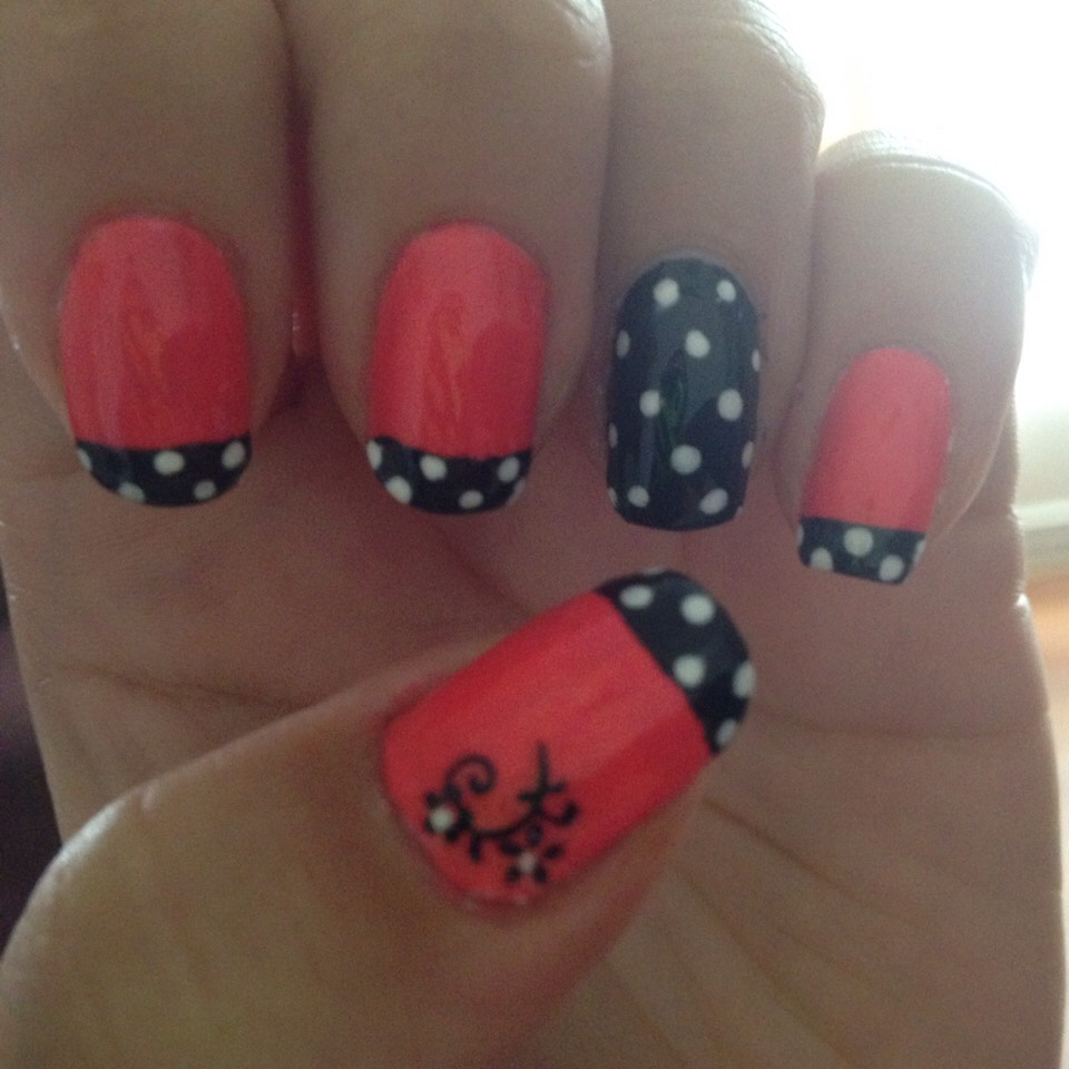 Pink nail with black top and white dots ; accent nail .. Black with white dots
