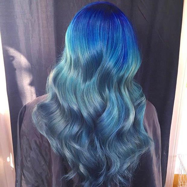 DARK BLUE TO LIGHT BLUE OMBRE: Products used to create this stunning mermaid look are Joico along with Rusk and Kenra. This type of color isn't easy to maintain. The style can get costly and time-consuming.