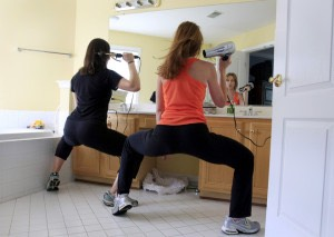 Instead of just standing still or sitting down. Use this time and do squats whilst drying or straightening your hair