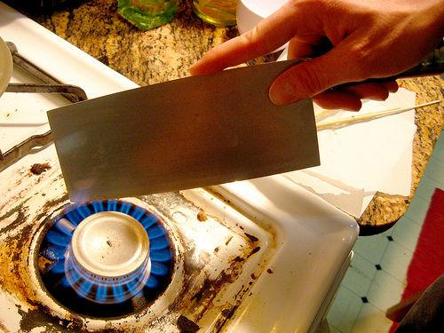 Place the blade of a large knife (not necessarily your best) directly into your burner to heat.  If you have an electric stove, you can use a lighter.  Once the blade is hot, begin to cut your sheets of sugar into strips.  Cut edges to be the length of a real slide.  Its good to have a glass slide t