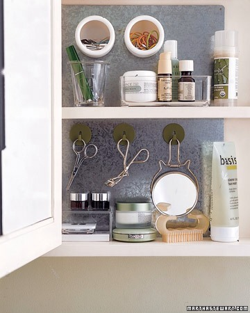 Galvanized Magnetic Vanity Backing  One big challenge with bathroom space is trying to fit a lot of little things into horizontal shelving. Take a tip from garage workshop organizers: hang your beauty tools vertically with this great idea.