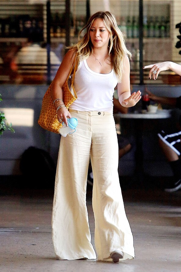 White tank, cream bell bottom pants. I know it's retro, but come on!!! This is the perfect outfit for an errand or a day by the beach. Hilary is keeping it real. 🐩