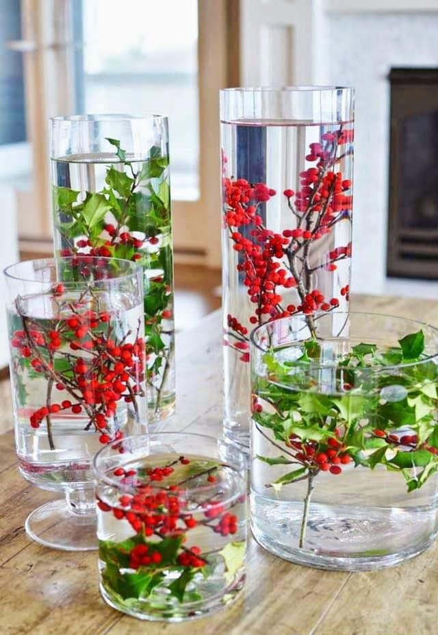 Natural elements are also easily accessible, affordable, and make for great holiday centerpieces. Here are a few examples of a more rustic look.Submerge some natural red and greens in large, water-filled vases for a modern rustic look, like these creations from33 Shades of Green.