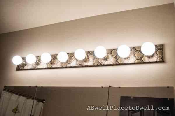 Duct tape comes in various colors and designs now. Unscrew light bulbs, trace holes   in duct tape, place on strip and voila! A snakeskin (or any other design) light fixture!