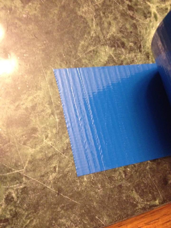 7. Cut 16 very thin pieces of the blue tape to put as the windows