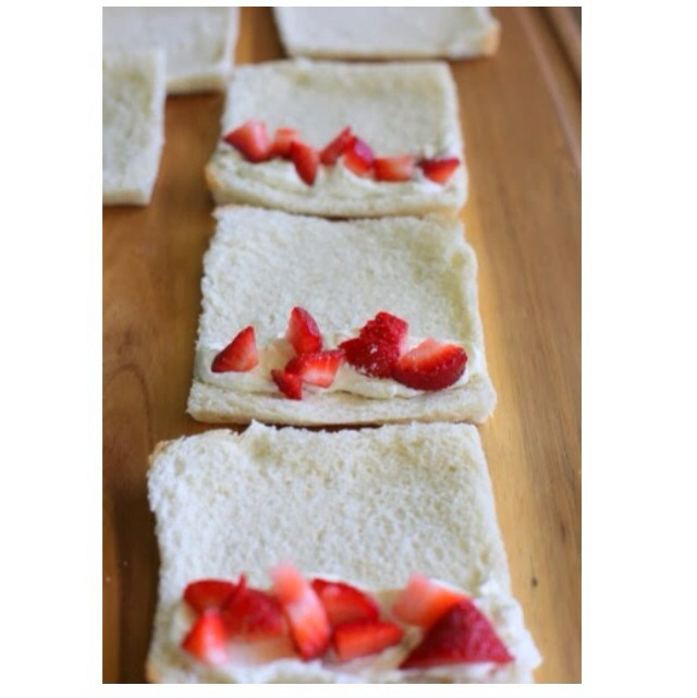 Cut the edges from the bread and roll them flat. After that place chopped strawberries on the bread as shown in the pictures!