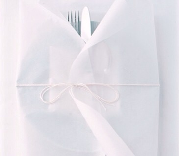 Parchment paper does double duty at the taIt makes an elegant place-setting wrap(who doesn't love paper packages tied up with string?)that unfurls to become a no-muss,no-fuss place mat.Tear off a 16-inch piece and lay it down against the curl-
