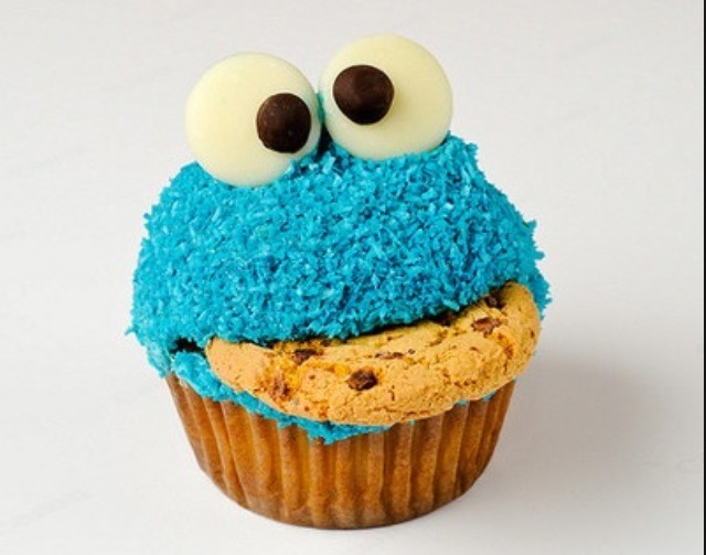 Cut out a piece of the cupcake to be able to fit the cookie. Use blue sprinkle flakes for the fur. This is sold at any baking supply store or supermarket. Use white chocolate with a dot of black frosting for the eyes.