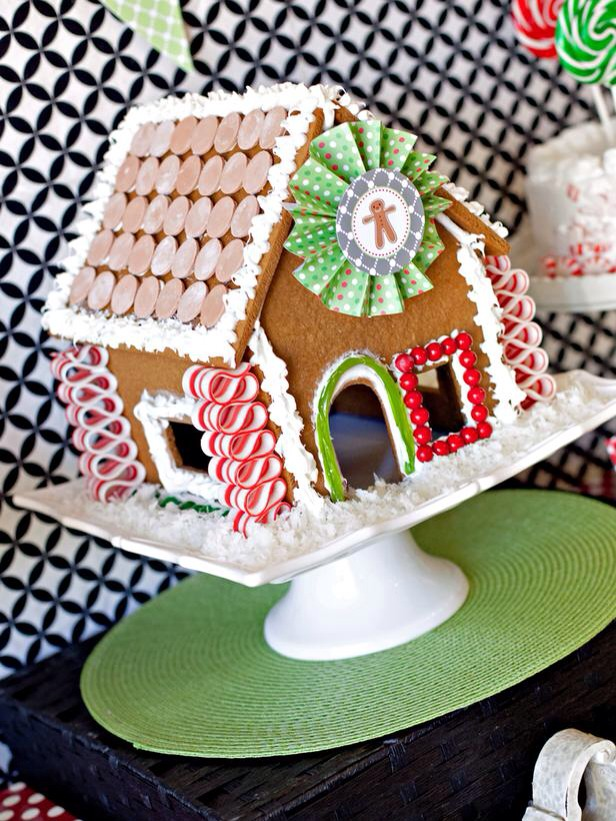 """Gingerbread House Centerpiece Turn this season's gingerbread masterpiece into a chic centerpiece for your holiday table. Let the kids help decorate it with candies and printable party circles, then set it in coconut """"snow"""" atop a cake stand."""