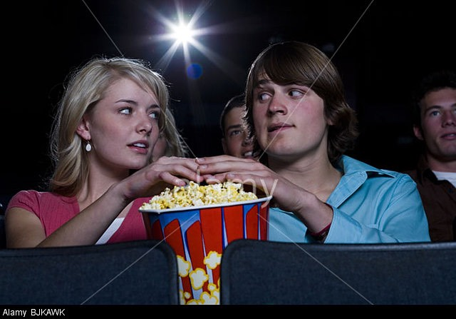 Keep an eye on him and wait until he reaches for the popcorn then when his hands reach the bucket then put yours in